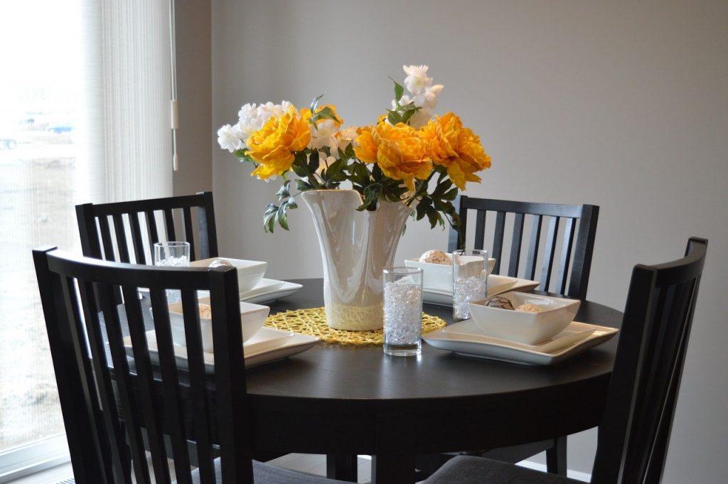 chaise noir en bois autour d une table ronde et des fleurs oranges