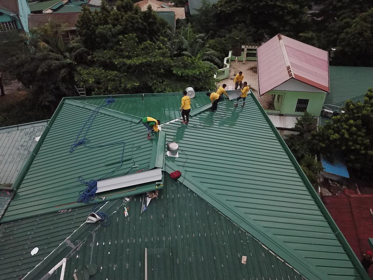 Couvreurs travaillant sur un toit vert