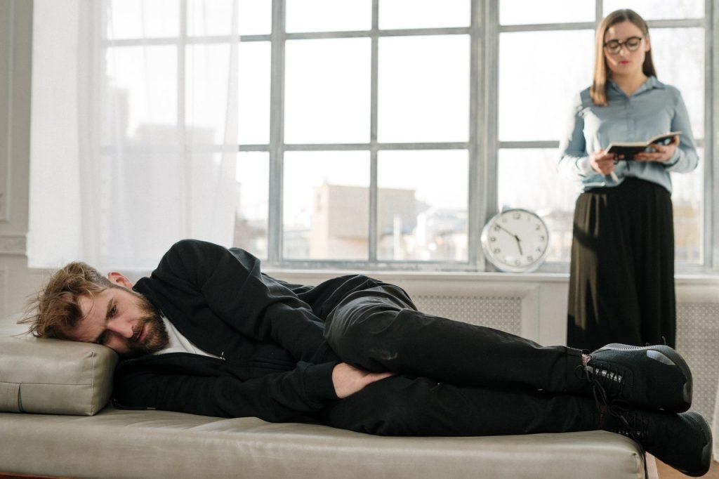homme en mal être allongé sur un sofa écoutant une femme