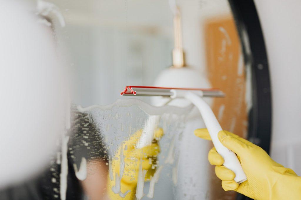 personne faisant du ménage lave vitre
