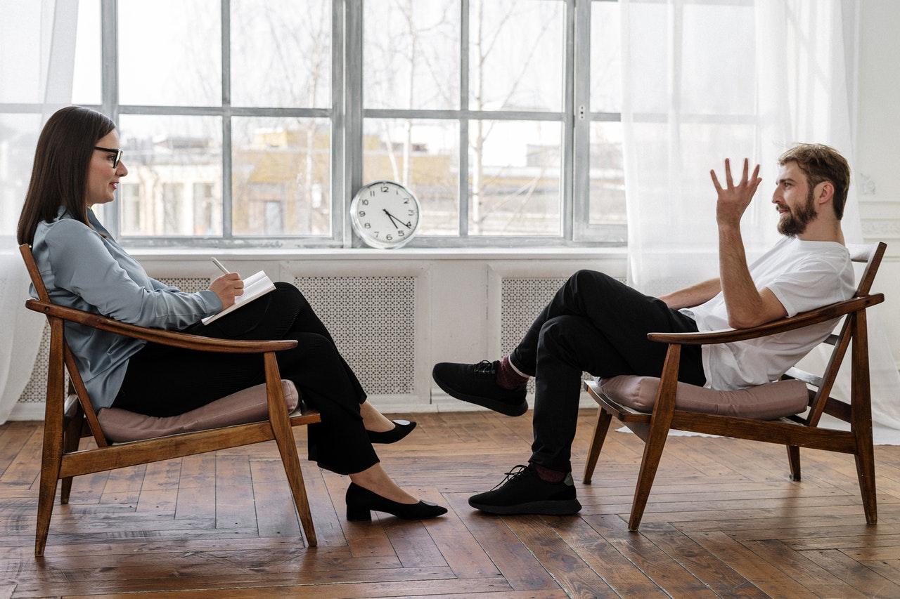 deux personnes homme et femme discutant assis fauteuil, séance psycologue