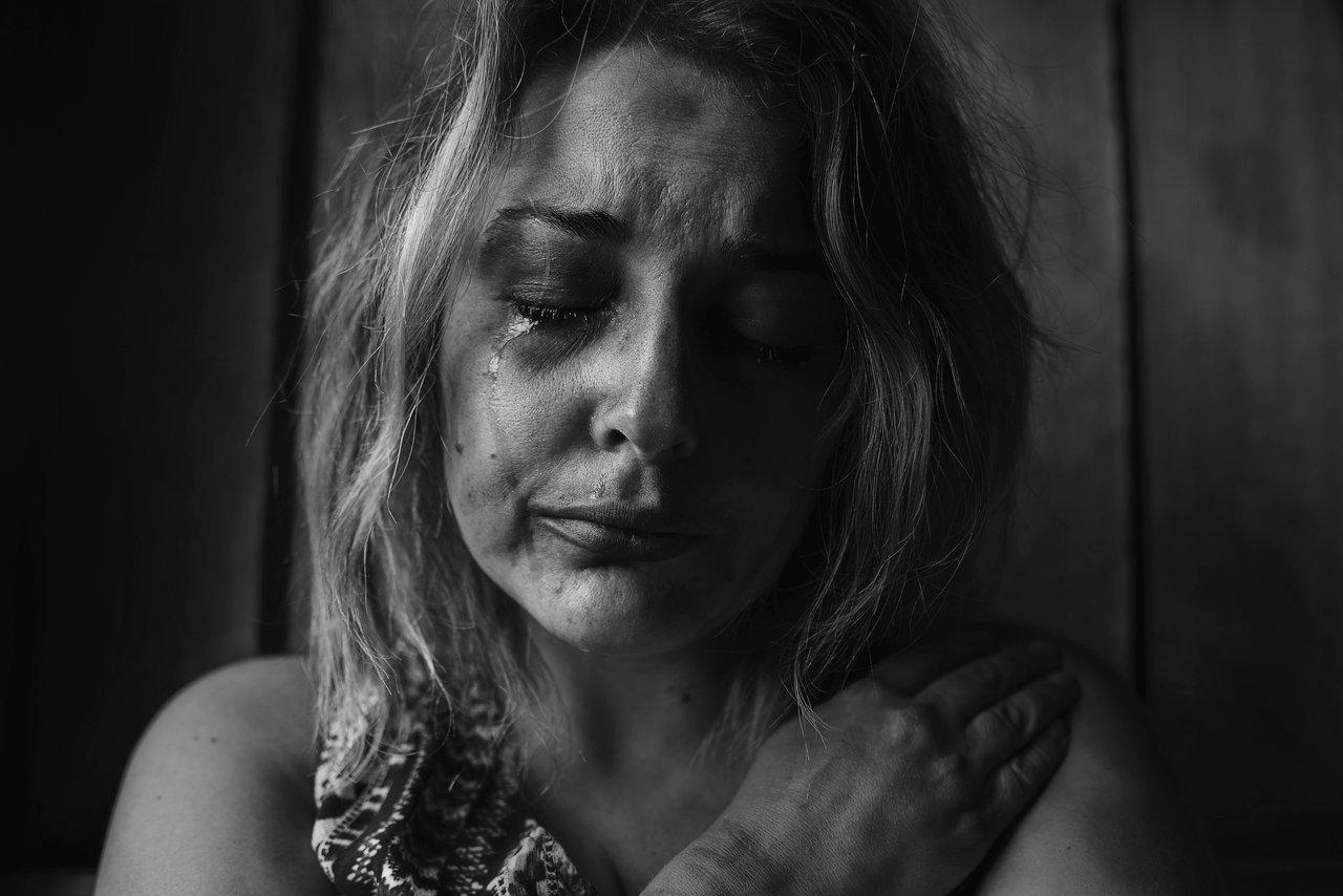 Photo en noir et blanc d'une femme ayant subit violence, peur, larme tristesse