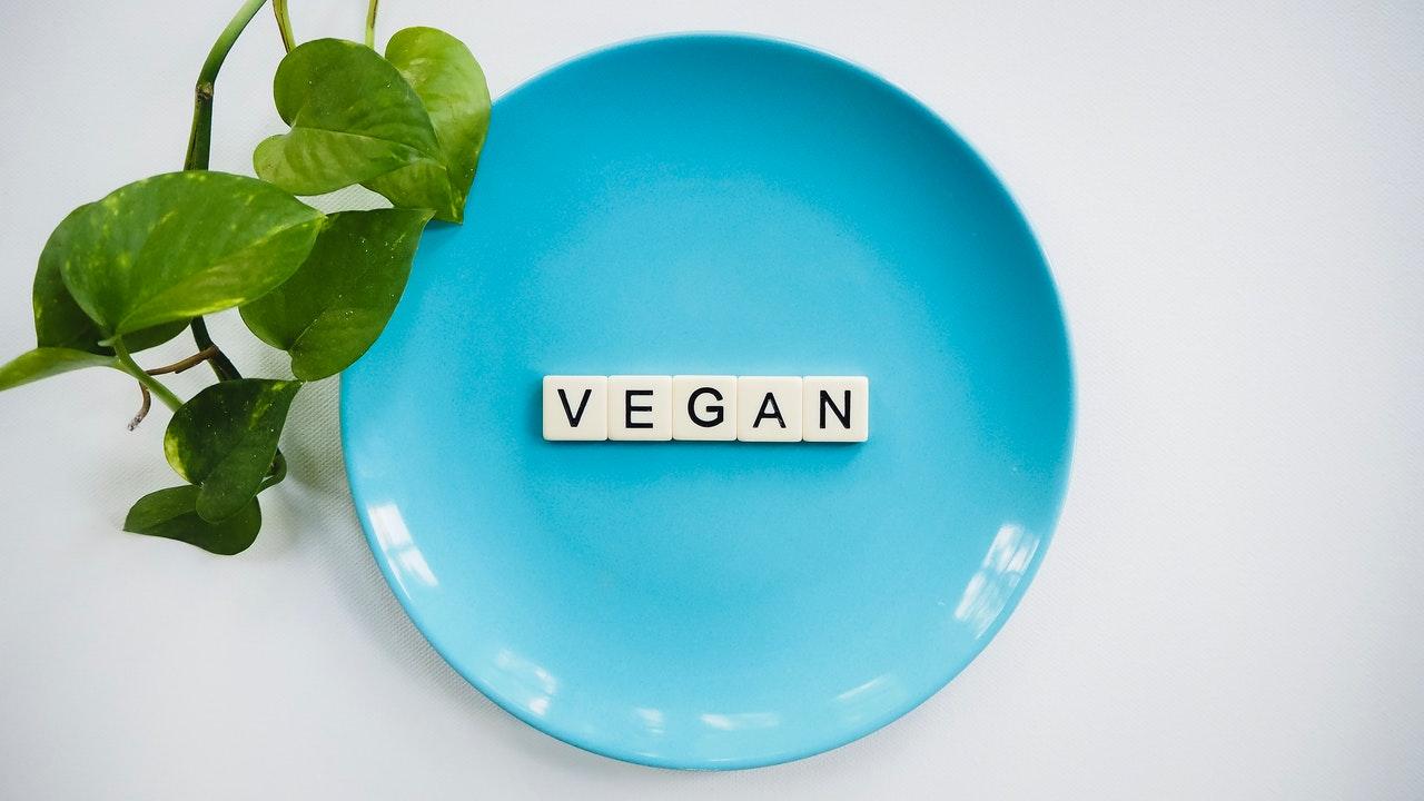 Assiette bleu avec des lettres de scrabble posées inscrivant Vegan