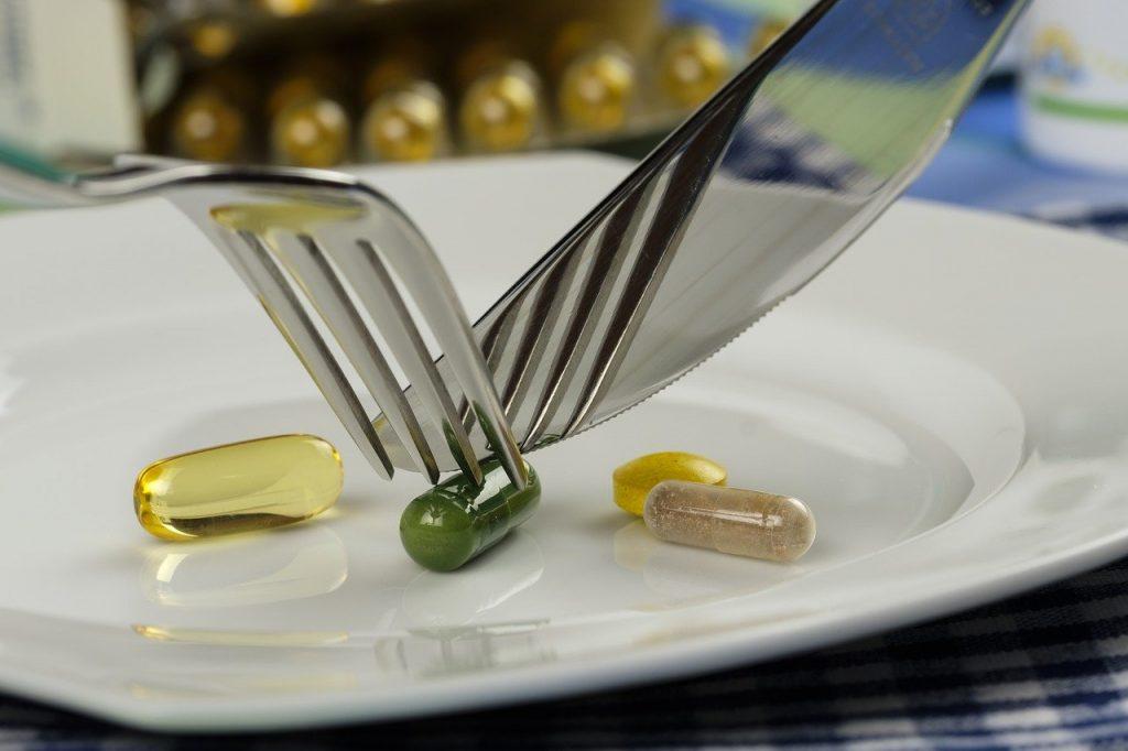 Pilules, représentant compléments alimentaire ou vitamine, dans une assiettes