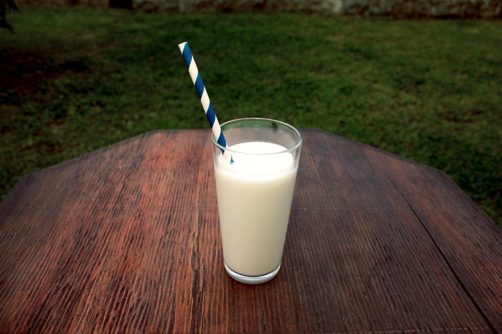 Verre de lait posé sur une table en bois avec une paille écologique