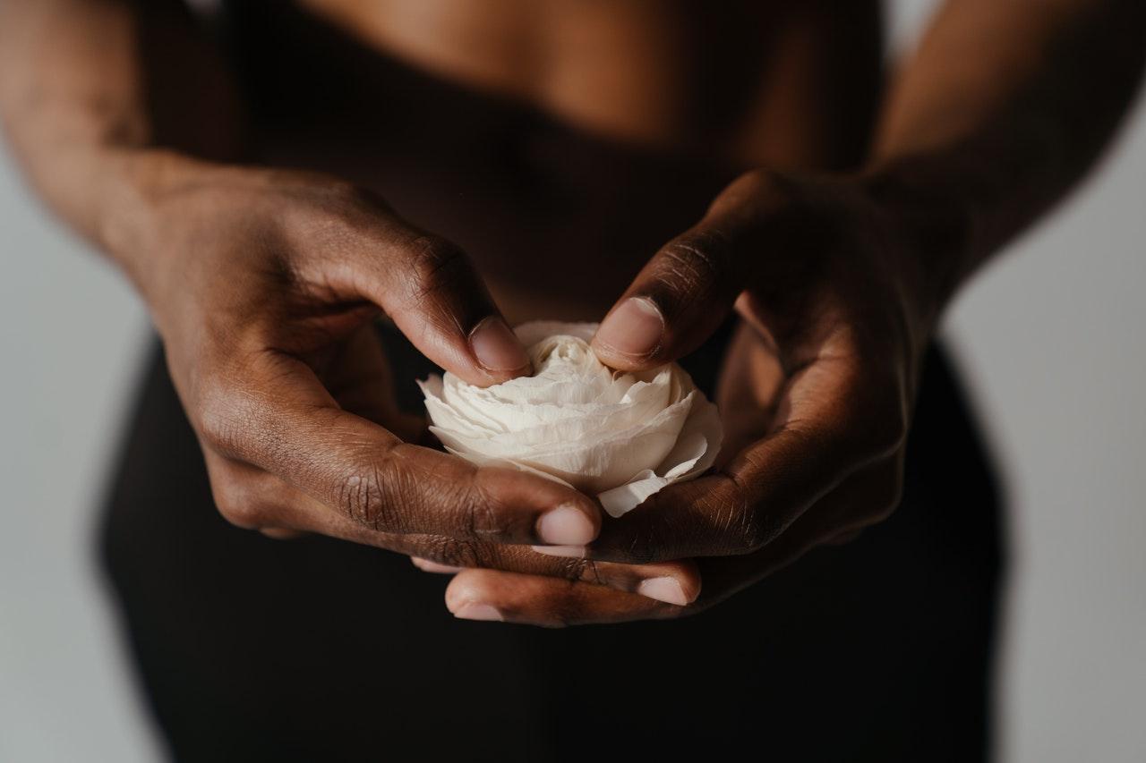Homme torse nu tenant une fleur blanche en main