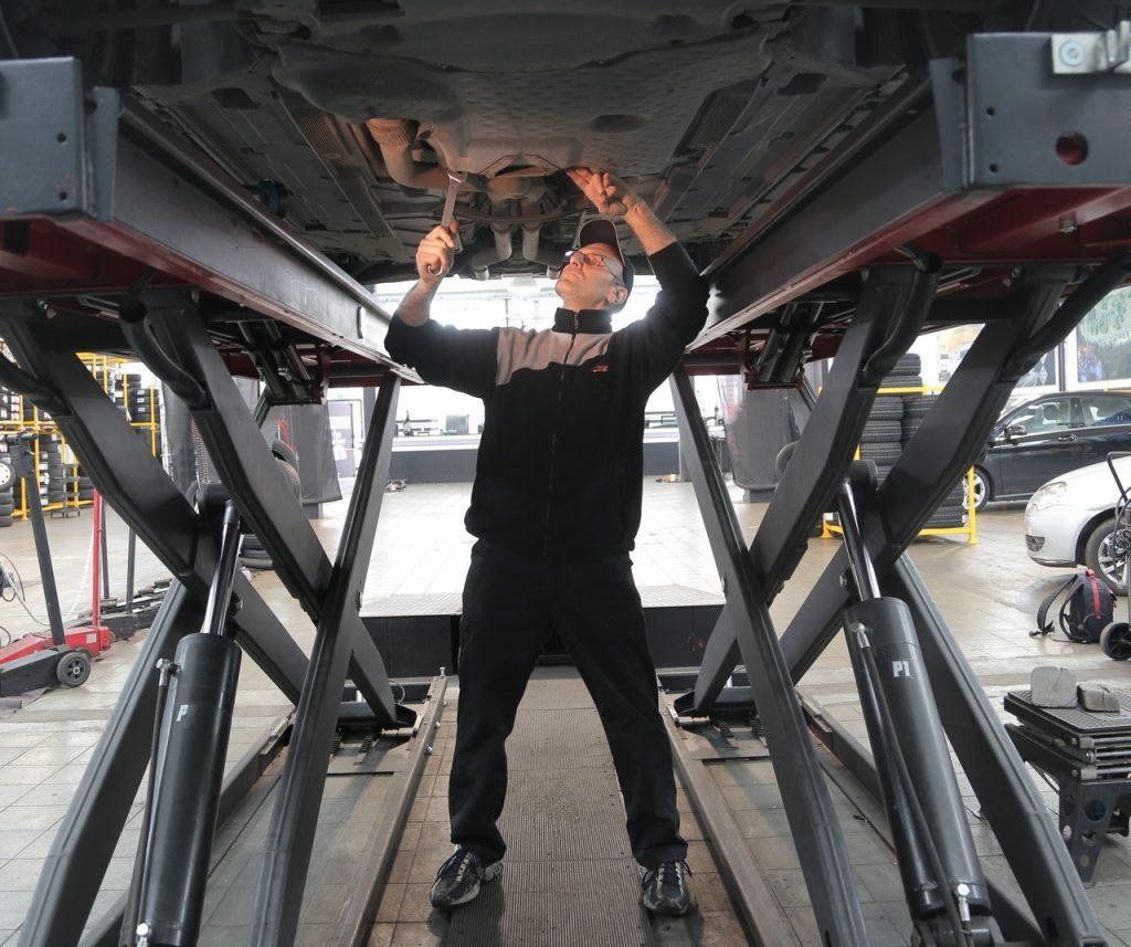 Garagiste sous un véhicule faisant un contrôle et des réparations