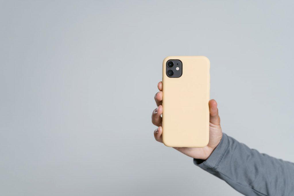 Main tenant un iPhone avec une coque jaune